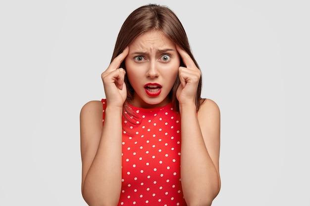 ネガティブな表情のコンセプト。暗いストレートの髪の不快なストレスの多い女性は、両方の寺院に人差し指を保ちます