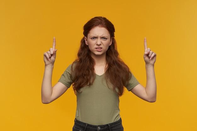 긴 생강 머리를 가진 부정적인, 찡그린 여자. 녹색 티셔츠를 입고. 사람과 감정 개념. 오렌지 벽 위에 절연 복사 공간에서 가리키는