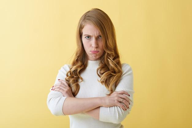 否定的な人間の感情と顔の表情。怒っている気まぐれな若い白人女性は、スタイリッシュなタートルネックの眉をひそめ、腕を組んで、夫が彼女の空想をユーモアを交わしていないためにイライラしています