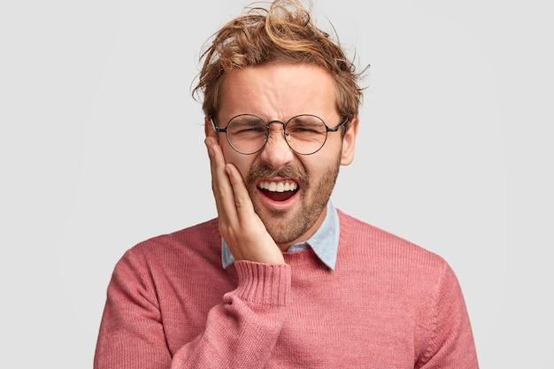 否定的な人間の感情や感情の概念。不機嫌な若い無精ひげを生やした男は歯痛に苦しんで顔をしかめ、頬に触れる