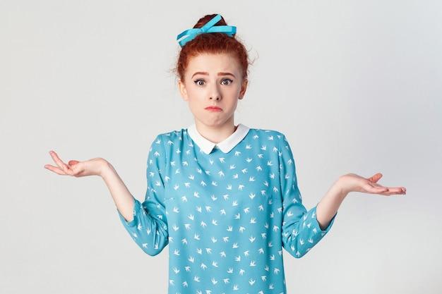 否定的な人間の感情、顔の表情、人生の認識と態度。腕を伸ばして困惑した若い赤毛の少女は、肩をすくめて言った。