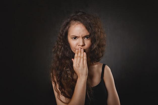 Emozioni umane negative ed espressioni facciali. foto di frustrato attraente giovane signora dai capelli scuri in sopracciglia aggrottate in alto nero e tenendo la mano sulle labbra, che soffrono di mal di denti