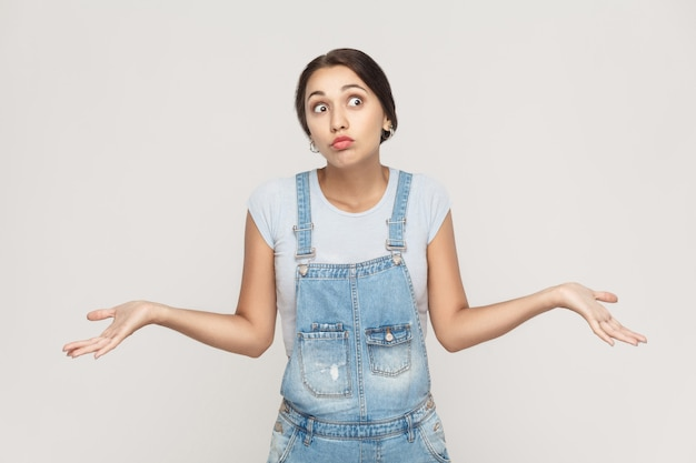 否定的な人間の感情、顔の表情。腕を組んで困惑した若い大人の女性が肩をすくめ、こう言った。灰色の背景で撮影された孤立したスタジオ。