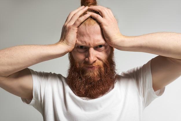 Emozioni, sentimenti, reazioni e atteggiamenti umani negativi. ritratto di stressato frustrato giovane uomo con la barba lunga che stringe la testa, sentendosi infastidito dal rumore, soffrendo di mal di testa, avendo un aspetto doloroso