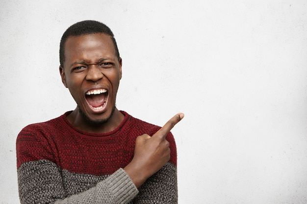 Negative human emotions. headshot of desperate furious young dark-skinned male dressed casually pointing his index finger sideways at white copy space wall, feeling mad and angry with something