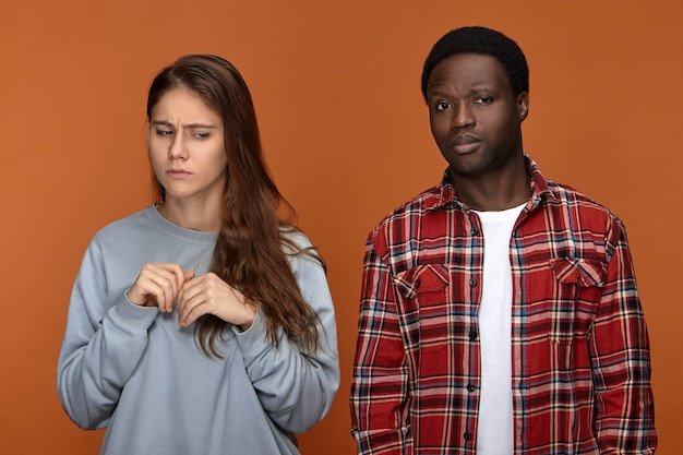 Negative human emotions and relationships concept. upset casually dressed young white female standing in closed posture, having worried look, being scared of her dark skinned husband abuser