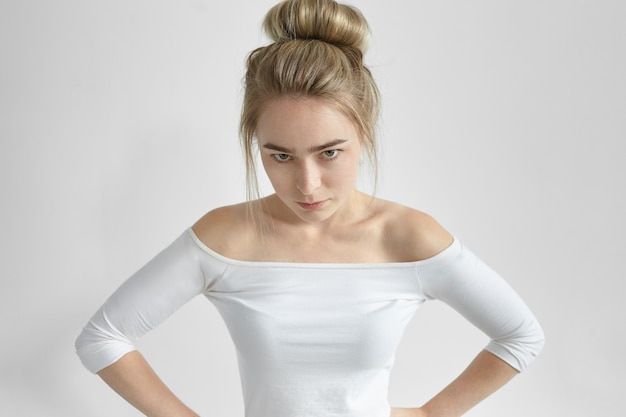 Negative human facial expression and reaction. isolated shot of angry annoyed young woman wearing open shoulder top looking sullenly
