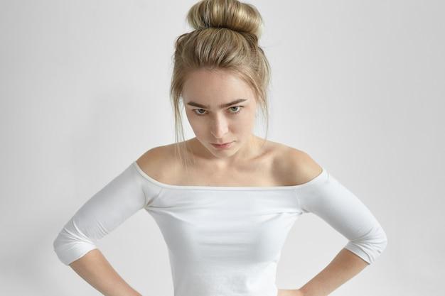 Espressione e reazione del viso umane negative. colpo isolato di arrabbiato infastidito giovane donna che indossa la parte superiore della spalla aperta guardando imbronciato