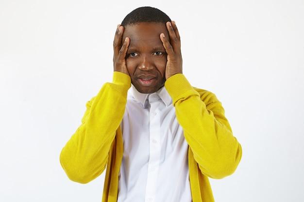부정적인 인간의 표정과 신체 언어. 감정적 인 어두운 피부의 남성은 스트레스와 좌절감을 느끼고 두 손을 머리에 얹고 공황 발작을 당하면 어떻게 해야할지 모릅니다.