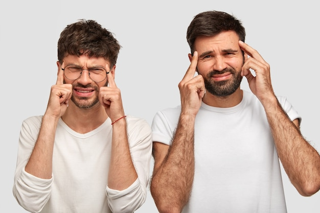否定的な人間の表情と感情。不機嫌な男性は、寺院に前指を置き、不満に顔をしかめ、頭痛に苦しみ、カジュアルな服を着ます