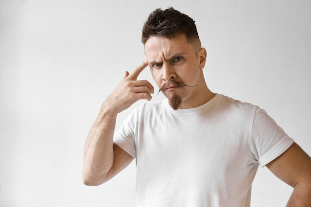 Espressioni facciali umane negative e linguaggio del corpo. foto di moda giovane barbuto hipster con divertenti baffi a manubrio in posa in studio, essere arrabbiato, rotolare il dito indice alla tempia