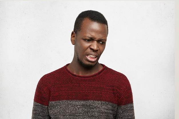 Espressioni facciali, emozioni e sentimenti umani negativi. ritratto di schifoso disgustato giovane maschio afroamericano che guarda terrorizzato e disprezzo, provando odio e disgusto verso qualcosa