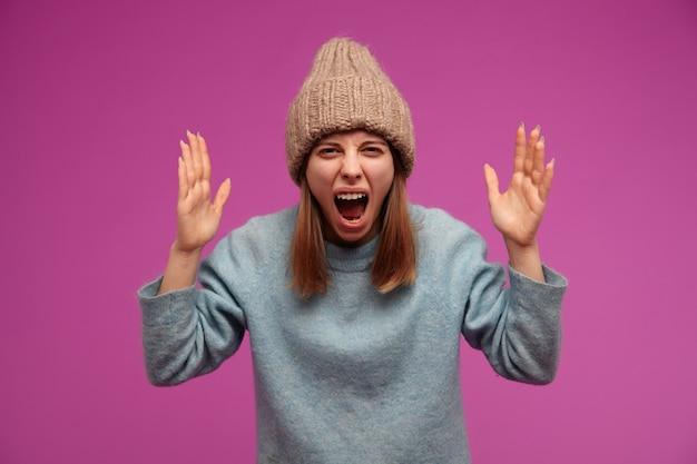 Donna dall'aspetto negativo, ragazza adulta con capelli castani. indossare maglione blu e cappello lavorato a maglia. alza le mani e urla di rabbia contro il muro viola