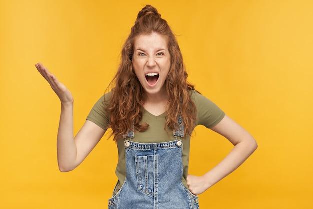 ネガティブで狂った生姜の女性は、青いデニムのオーバーオールと緑のtシャツを着て、悲鳴を上げ、ネガティブな表情で手を上げました。黄色の壁に隔離