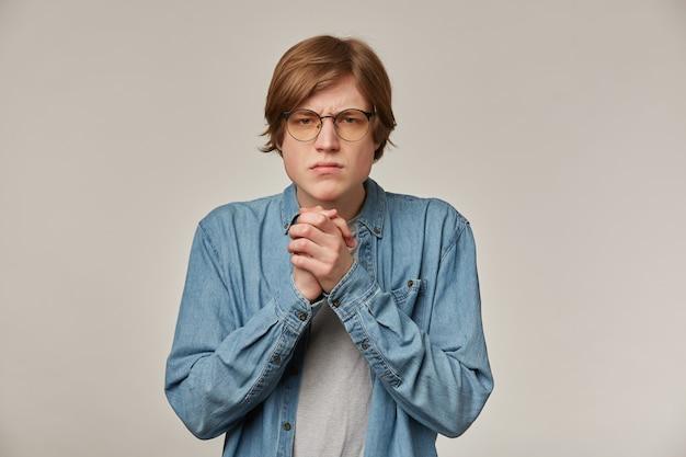 Негативный мужчина, ревнивый парень со светлыми волосами. в джинсовой рубашке и очках. потирает ладони и хмурится. концепция людей и эмоций. наблюдая за сердитым изолированным над серой стеной
