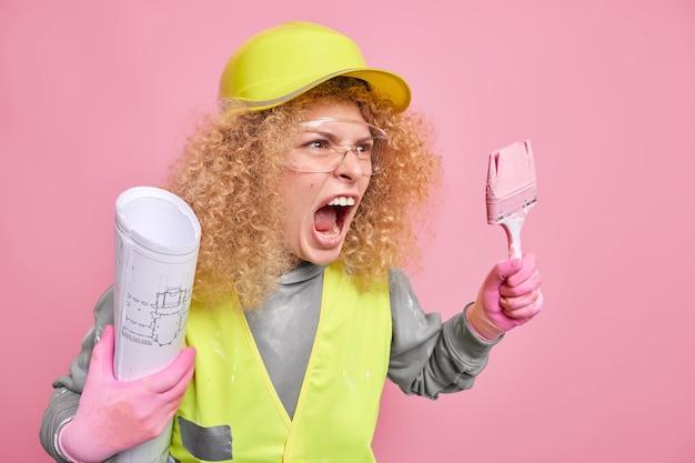 격분한 전문 장식가는 아파트 벽에 페인트 붓 종이 건축 청사진을 들고 헬멧 보호복을 입고 실내 포즈를 취하는 누군가에게 화를 내고 있습니다. 집 수리