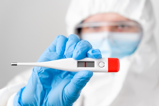 Negative pregnancy test in doctors hand in protective suit ppe, rubber gloves, face mask, safety