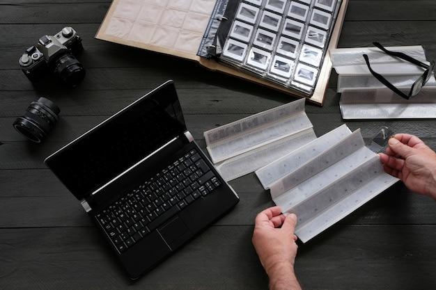 アナログ写真機材とラップトップを備えたネガと写真スライド