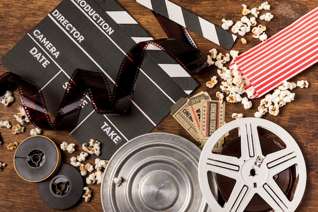 Negatives stripes with clapperboard; film reels; tickets and popcorn on wooden desk