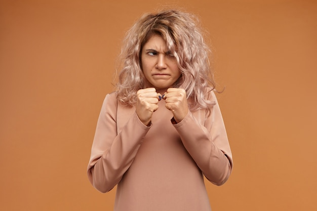 Negativity, aggression and rage concept. funny emotional young caucasian woman frowning, holding clenched fists in front of her, ready to punch enemy