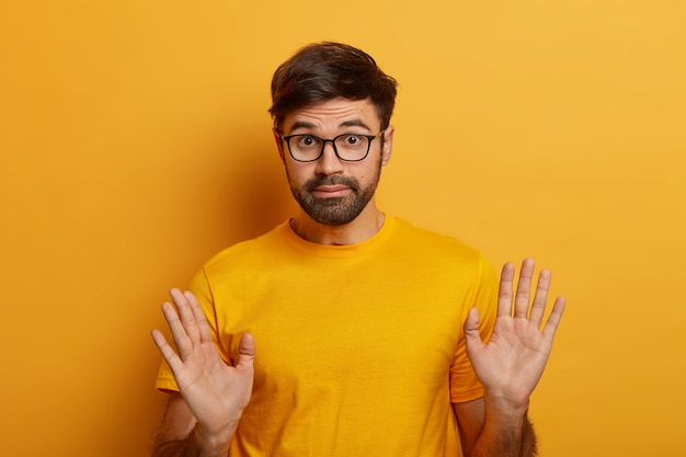 Negligence concept. bearded young man expresses carefree responsibilty, says not my problem at all, raises palms , wears spectacles and casual t shirt, being uninvolved in something