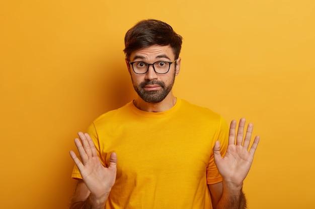 過失の概念。ひげを生やした若い男はのんきな責任を表明し、私の問題はまったくないと言い、手のひらを上げ、眼鏡とカジュアルなtシャツを着て、何かに関与していません