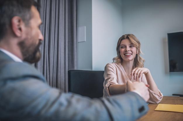 交渉、合意。オフィス交渉で向かいに座っているビジネス大人のパートナーに手を振るブロンドの髪を持つ若い美しいうれしそうな女性