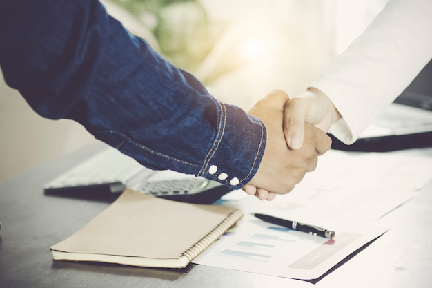 Negotiations and business success concept, businessmen shaking hands or handshake in offic
