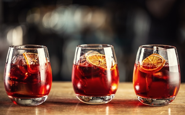 Negroni classic cocktail and gin short drink with sweet vermouth, red bitter liqueur and dried orange garnish.