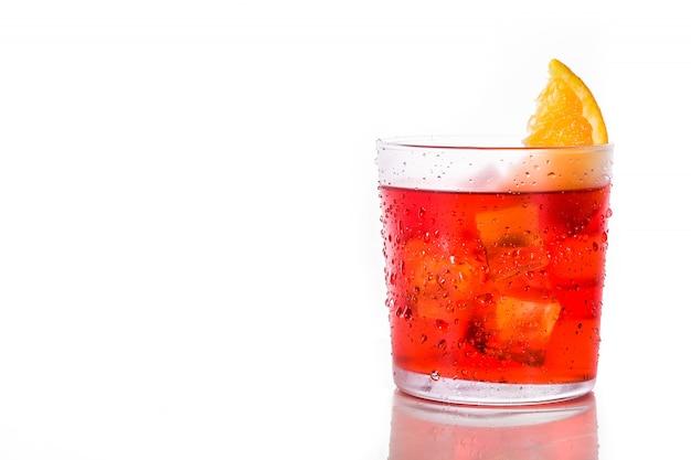 Negroni коктейль с кусочком апельсина в стакане, изолированных на белом, copyspace