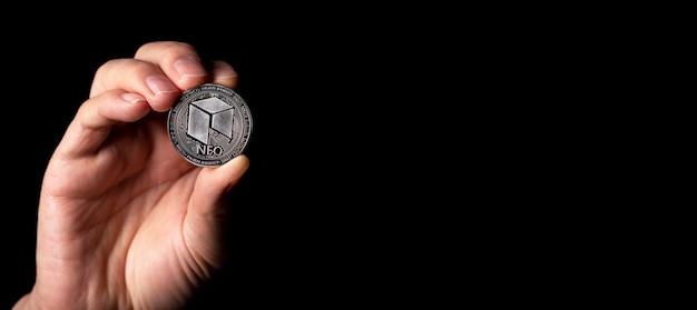 テキストのコピースペースと黒の背景の上に男性の手でネオ光沢のある銀貨