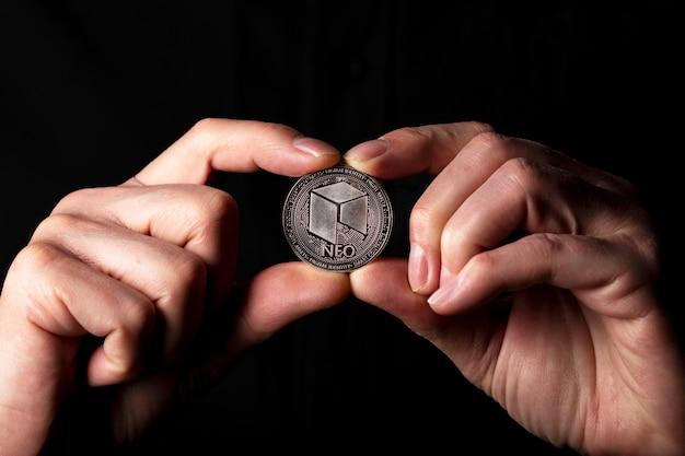 黒の背景の上に男性の手でneo光沢のある銀貨。