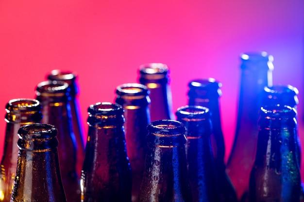 ネオン色のビール瓶が明るいスタジオの背景にクローズアップ
