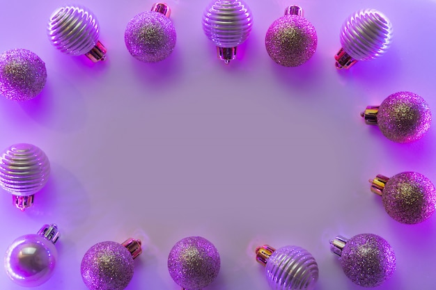 Neon frame on silver christmas balls in colorful purple rays. top view. xmas.