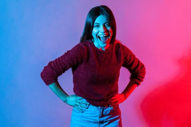 Неоновый свет портрет радостной беззаботной женщины, держащей живот и громко смеющейся