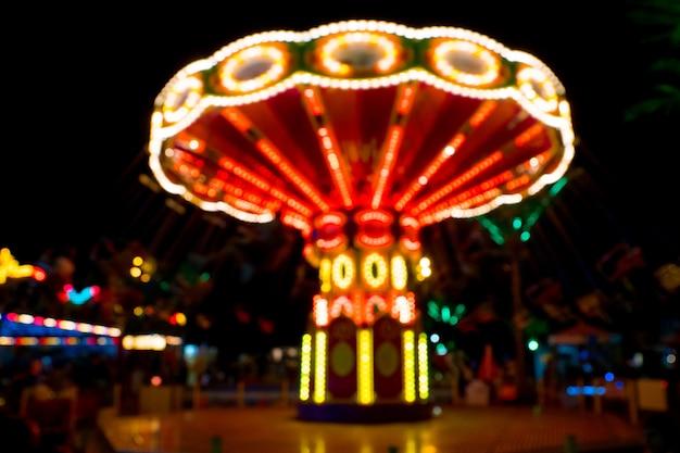Неоновые огни на цепной карусели в парке развлечений