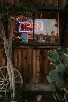 Неоновая открытая вывеска в окне ресторана