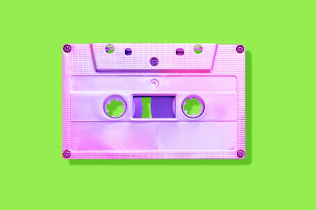 Neon pink cassette tape on a green background with shadow