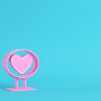 Neon, pink heart shape in frame on bright blue background