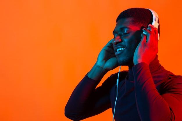 Neon portrait of handsome african american man in headphones. listening to music.