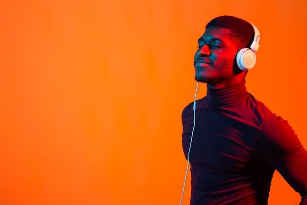 Неоновый портрет молодого африканца, слушающего музыку с наушниками. оранжевая стена с копией пространства