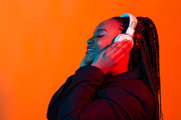이어폰으로 젊은 아프리카 여자 듣는 음악의 네온 초상화.