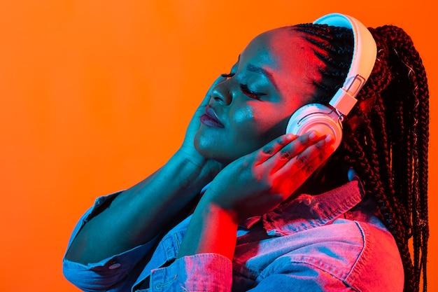 젊은 흑인 여자의 네온 초상화는 헤드폰에서 음악을 듣습니다.