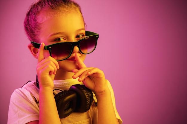 Неоновый портрет молодой девушки с наушниками, наслаждающейся музыкой и призывающей к тишине.