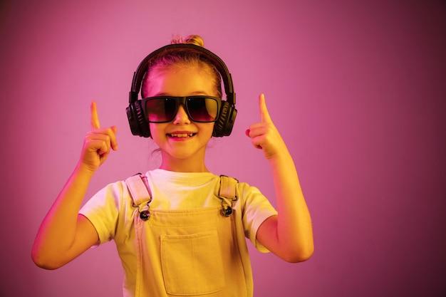 Неоновый портрет молодой девушки с наушниками, наслаждающейся музыкой. образ жизни молодых людей, человеческие эмоции, детство, концепция счастья.