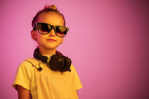 Неоновый портрет молодой девушки с наушниками, наслаждающейся музыкой.