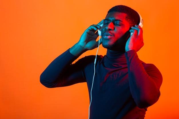Neon portrait of young african man listening music with earphones.