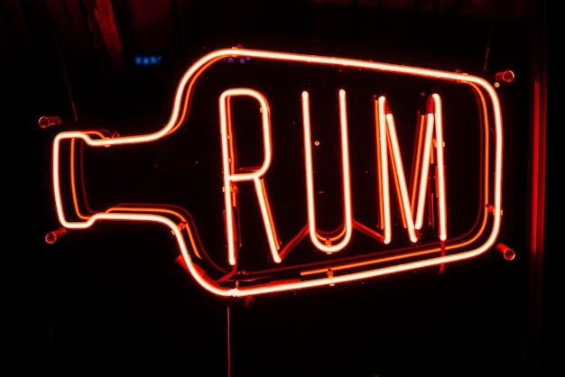 Неоновая вывеска в баре с текстом ром