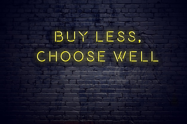 Neon sign with positive wise motivational quote against brick wall