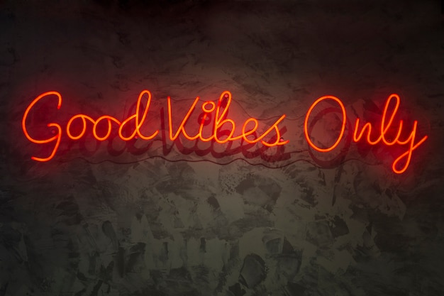 Neon with the word good vibes only, on wall texture.